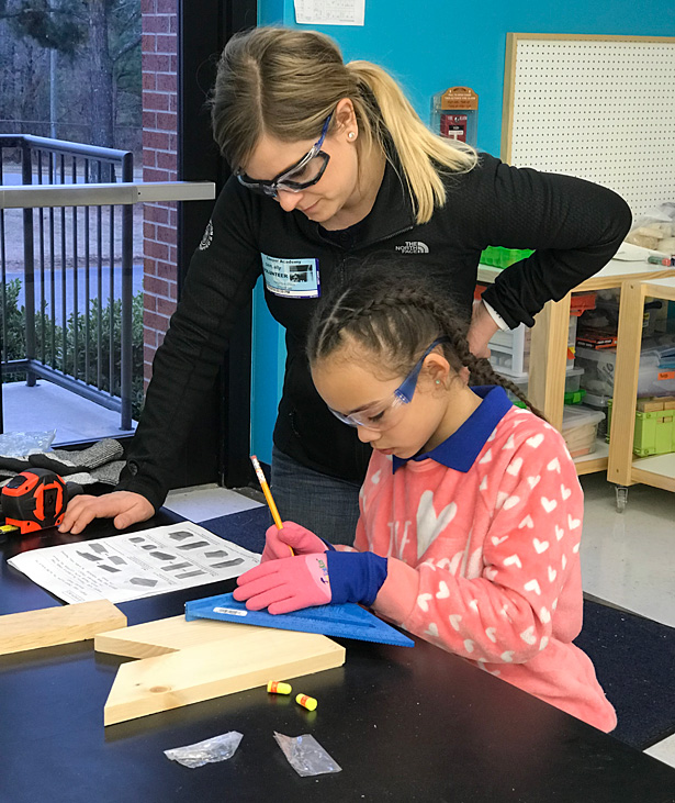Fluor employee Ally Cain helps student build a butterfly house
