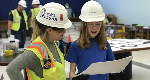 Fluor volunteer explains the construction process to a student